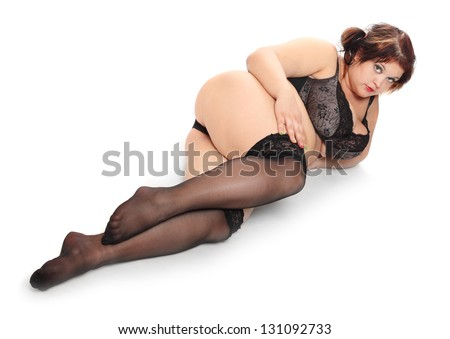 Overweight woman dressed in retro lingerie on a white background. - stock photo