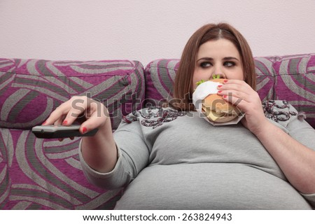 Overweight woman eating a burger and watching tv - stock photo