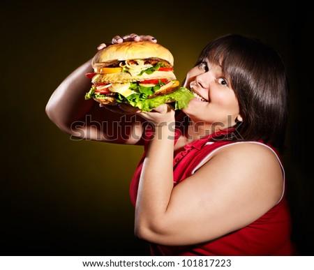 Overweight woman eating hamburger. - stock photo