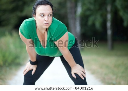 Overweight woman exhausted after a long run. Selective focus. - stock photo
