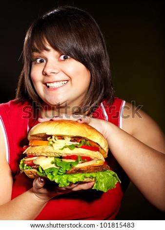 Overweight woman holding big hamburger. - stock photo