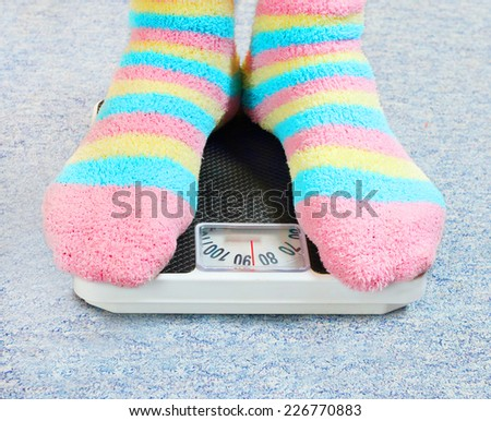 Overweight woman in funny socks standing on a retro style weighing machine. - stock photo
