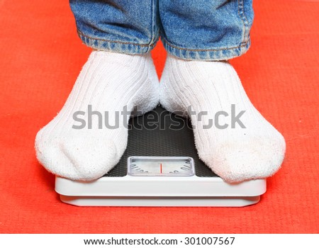Overweight woman in socks standing on a weighing machine. - stock photo