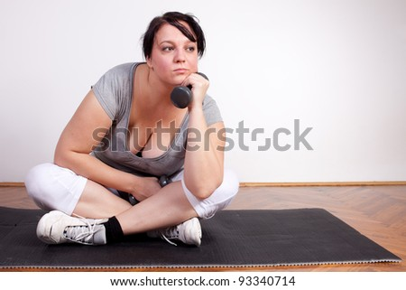 Overweight woman is sick and tired of exercising - stock photo