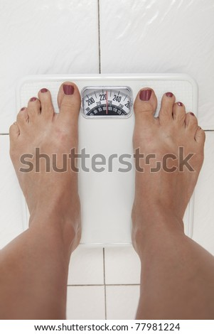 Overweight woman looking at weigh scale - stock photo