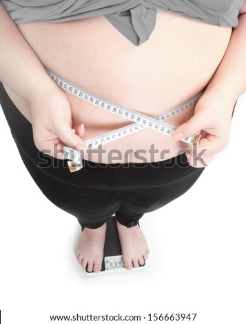 Overweight woman measure her waist belly by metre-stick on a weighing machine.  - stock photo