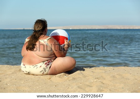 overweight woman sitting with ball on beach near sea  - stock photo