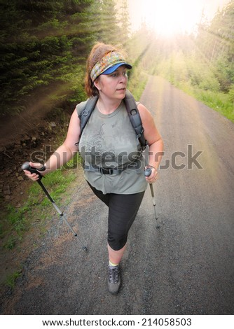 Overweight woman walking in nature. Healthy lifestyle and weight loss concept. - stock photo