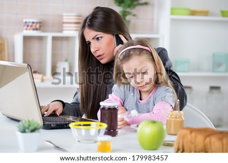 Overworked Business Woman and her little daughter in the morning. Mother read mail and make phone calls before going to work. Daughter salt breakfast. - stock photo