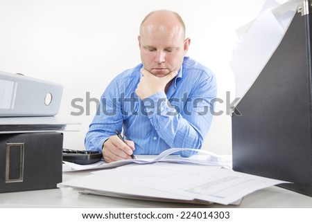 Overworked businessman at the office - stock photo