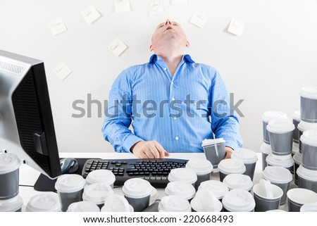 Overworked businessman drinks too much coffee - stock photo