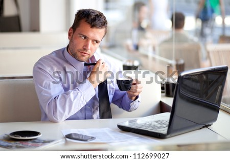 Overworked businessman untying his tie in a cafe - stock photo