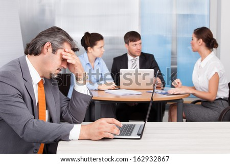 Overworked Businessman With Laptop Sitting In Front Of His Coworkers - stock photo
