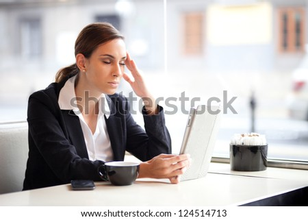 Overworked businesswoman in a coffee shop - stock photo
