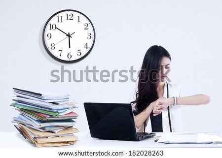 Overworked businesswoman looking at a clock. shoot at workplace - stock photo