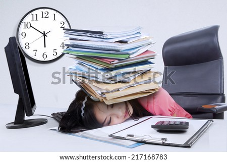 Overworked businesswoman sleeping in office with a pile of document on her head - stock photo