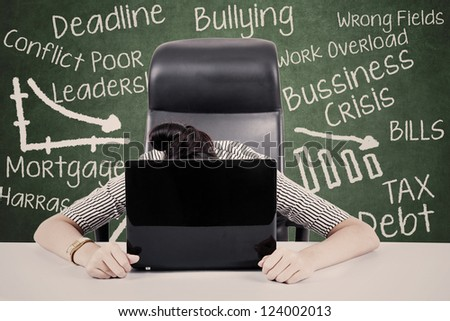 Overworked businesswoman with her face on keyboard of laptop. Shot at workplace - stock photo