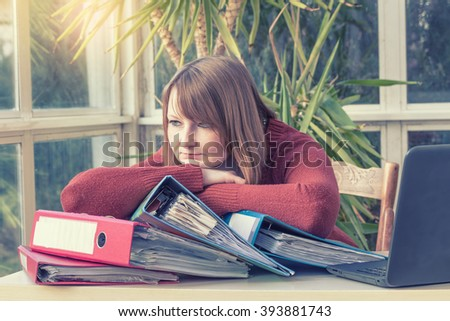 Overworked caucasian young woman is sitting at an office desk. Photo is edited as instagram effect with light in the upper left edge. - stock photo