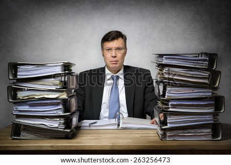 Overworked depressed businessman with lot of files on his desk - stock photo