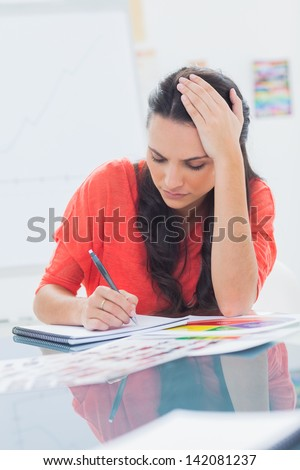 Overworked designer holding her head while she is drawing on a notepad - stock photo
