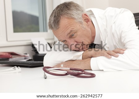 Overworked doctor having burn out - stock photo