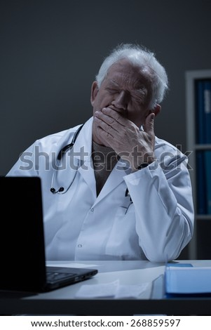 Overworked doctor sitting at the desk and yawning - stock photo