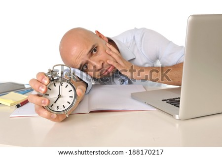 Overworked , tired and exhausted bald latin business man with computer and notepads at office desk holding alarm clock in extra time long hours working concept  - stock photo