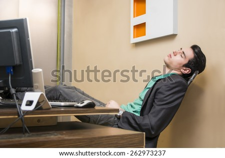 Overworked, tired young businessman sleeping at his desk  in office, in front of computer - stock photo