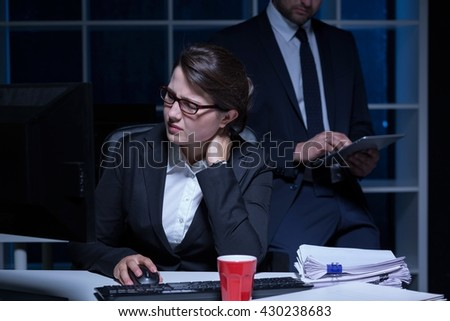 Overworked woman working at office, at night, in the background man using his tablet - stock photo
