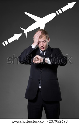 Overworked young businessman being late on airplane - stock photo
