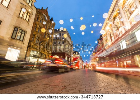 Oxford street in London with Christmas lights and blurred traffic. It is one of the busiest street of the capital city of England, and during Christmas time it becomes magic and fairy. - stock photo