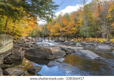 Oxtongue River in autumn with vibrant fall colors reflecting on its surface - Ontario, Canada - stock photo
