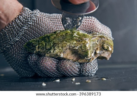 Oyster in hand with knife - stock photo