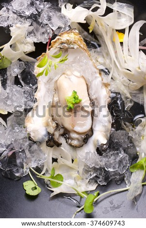 Oyster on the half shell with fennel salad and seaweed. - stock photo