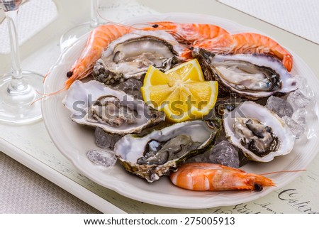 oysters shell, jumbo shrimp with lemon on ice, top view - stock photo