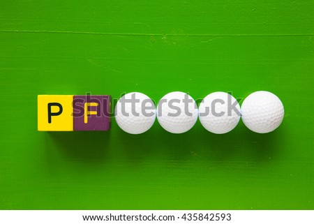 P.F. - an inscription from children's wooden blocks and golf ball  - stock photo