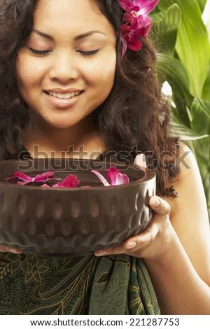 Pacific Islander woman holding spa treatment bowl - stock photo