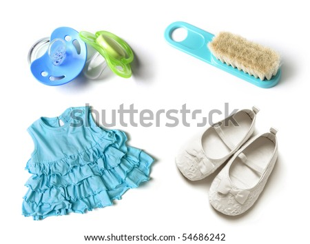 pacifiers, baby hairbrush, baby girl dress and baby shoes - stock photo