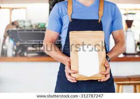 Package design template mockup. Man holding blank coffee package - stock photo