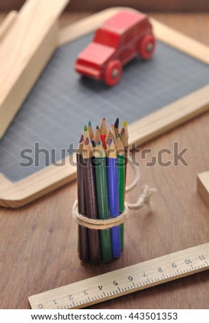 package of colored pencils with slate, rule  and toy  on a wooden background - stock photo