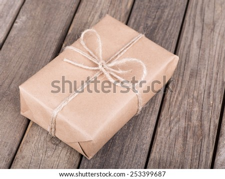 Package wrapped in brown paper and string on old wooden planks - stock photo