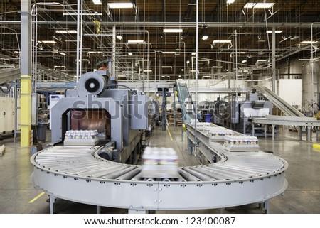 Packed bottle moving on conveyor belt - stock photo