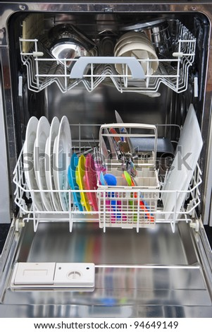 Packed dishwasher of clean dishes for a family - stock photo