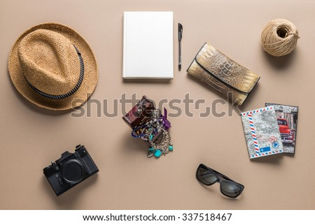 Packed suitcase of vacation items on wooden table, top view - stock photo