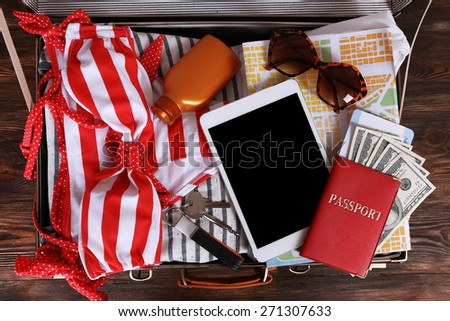 Packed suitcase of vacation items, top view - stock photo