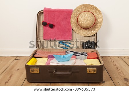 Packed suitcase with sun glasses and beach hat - stock photo
