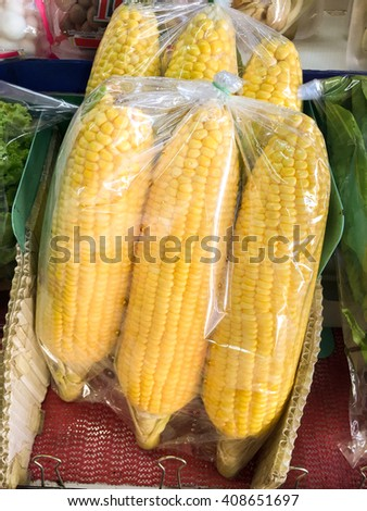 Packs of boiled yellow corn for sale in market - outdoor lighting - stock photo