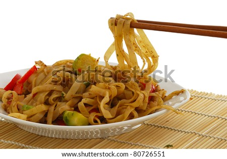 Pad Thai dish on straw pad with chopsticks isolated on white background - stock photo