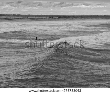 Paddle surfer going out at second beach in Newport RI. - stock photo