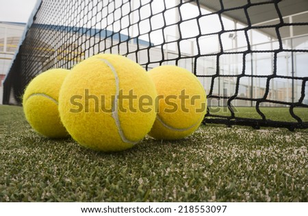 Paddle tennis objects on turf with net background - stock photo
